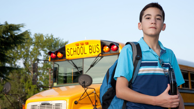 A young hispanic teen in front of the school bus.