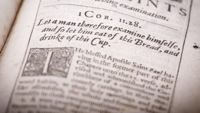 Detail of page from an ancient religious Christian text from the 1600s. Printed in old English language and typography. Shallow depth of field--focus on 1 Corinthians 11:28 scriptural reference.