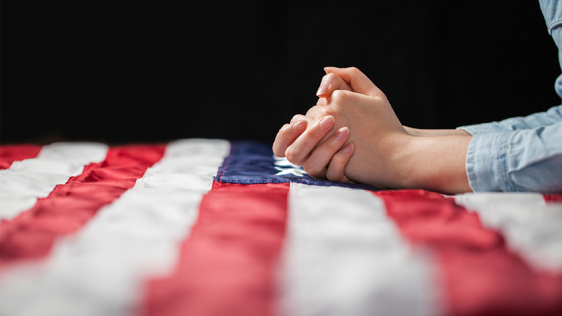 Hands praying over american flag