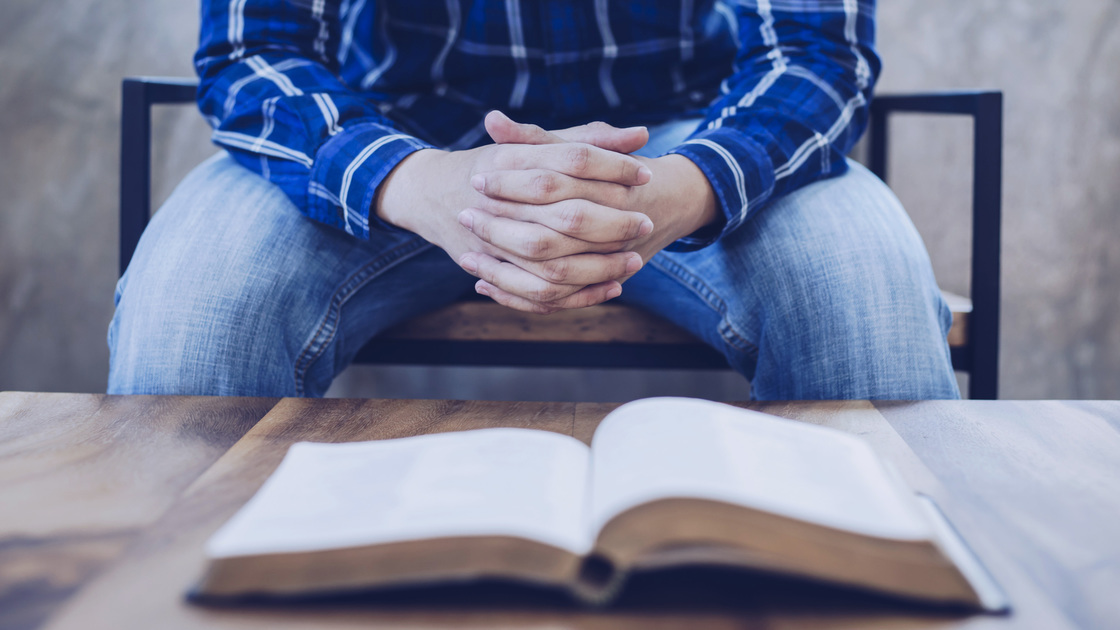 A man sitting on wooden chair praying to God with blurred open bible on wooden table foreground, trust concept