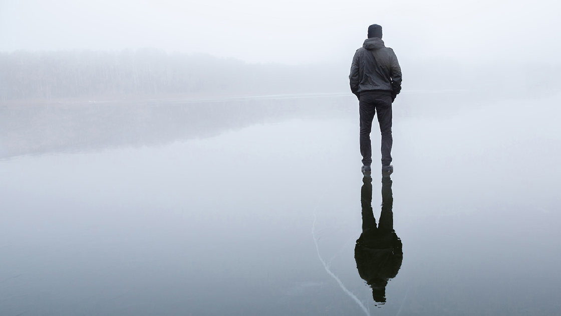 Young adult man standing alone on cracked dark ice surface. Mist over frozen lake in winter. Foggy air. Early chilly morning. Peaceful atmosphere in nature. Back view.
