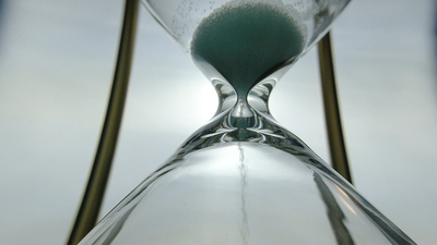 Extreme close up view of sand flowing through an hour glass. Super closeup of hourglass clock middle.  Classic sandglass timer countdown.