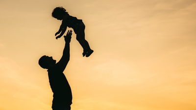 Father throwing his daughter in the air at sunset.