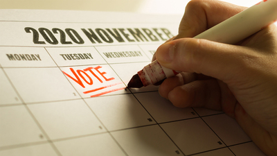 A american vote writing a reminder note on the calender to vote.