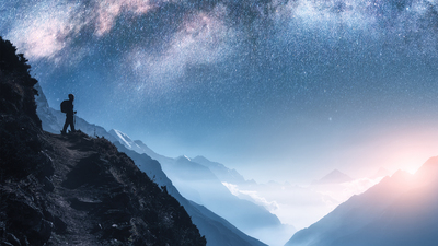 Arched Milky Way, woman and mountains at night. Silhouette of standing girl on the mountain peak, mountains in low clouds and starry sky in Nepal. Space landscape with bright milky way arch. Travel
