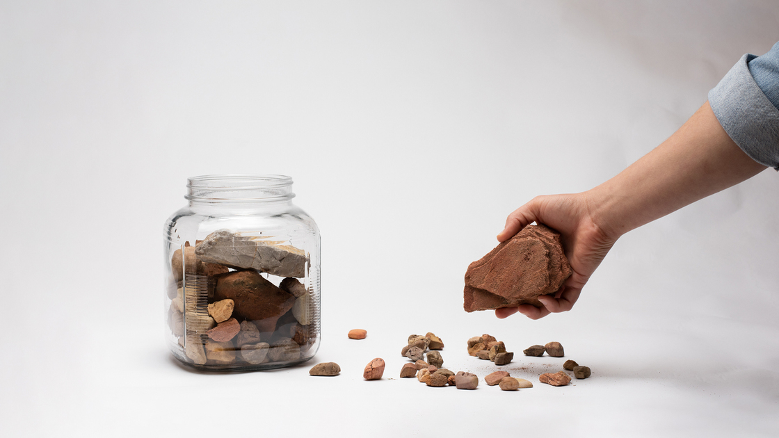 Hand putting rocks in a large jar